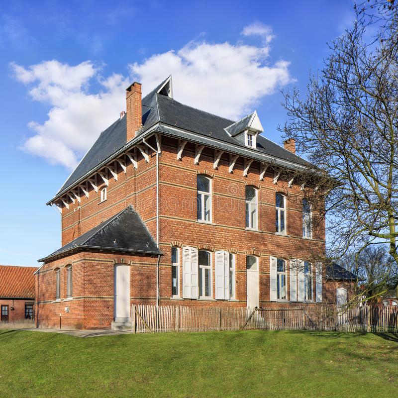 Stately parsonage againts a blue sky with dramatic clouds, Ravels, Belgium. Stately ancient parsonage against cloudy blue sky, Ravels, Flanders, Belgium stock image