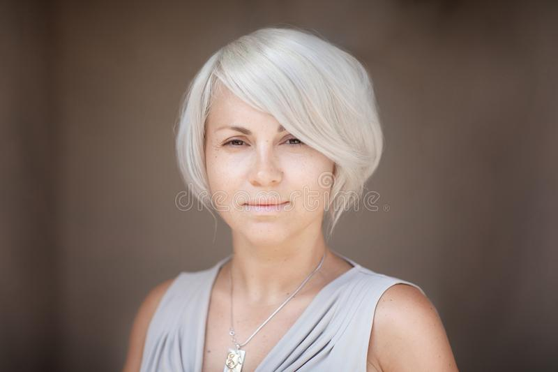 Stately serious blond woman looking solemnly directly in the camera. Blurred brown background. Stately serious blond woman looking solemnly directly in the stock image
