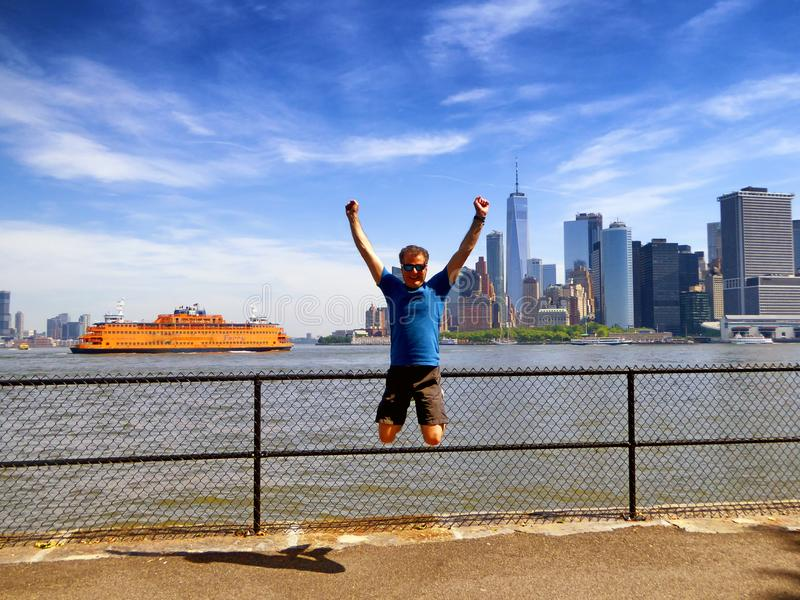 Staten island ferry with Lower Manhattan background. A middle aged man jumping with Staten island ferry and lower Manhattan skyline background in New York United stock photo