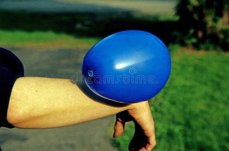 Static electricity. Blue balloon attached to caucasian woman's wrist and  forearm royalty free stock images