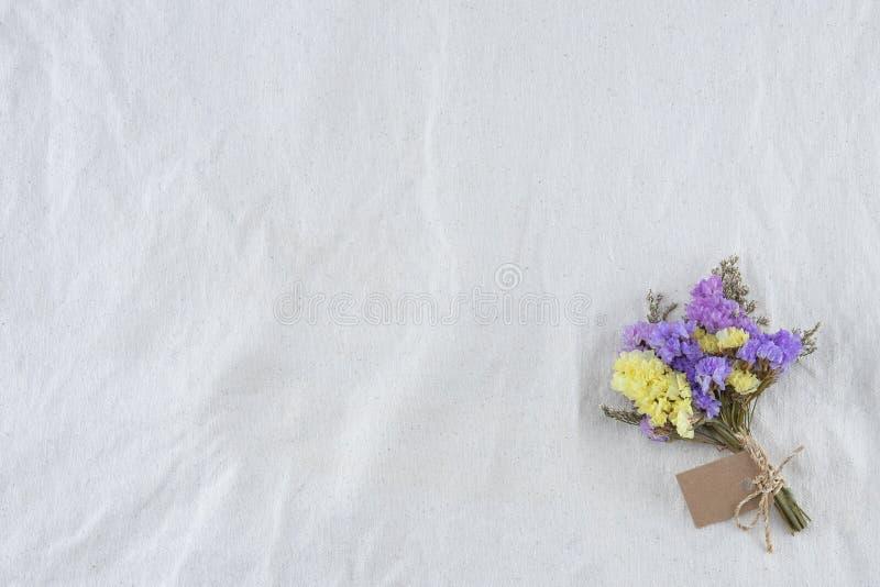 Statice fiorisce il mazzo con la carta sul tessuto bianco della mussola fotografia stock