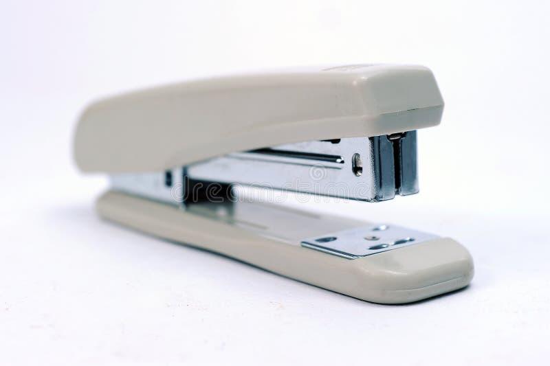 Stationär grå häftapparat för kontor med högen av häftklamrar royaltyfria foton