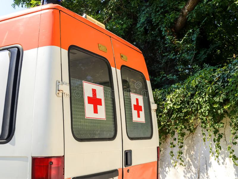 Stationäres weißes Krankenwagenauto mit roten Kreuzen auf den Fenstern an einem sonnigen Sommertag Ein Packwagen der Notärztliche lizenzfreies stockbild