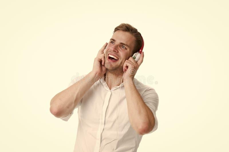 Station de radio préférée Équipez la chanson préférée de écoute dans des écouteurs avec le smartphone et le chant L'homme appréci photo libre de droits