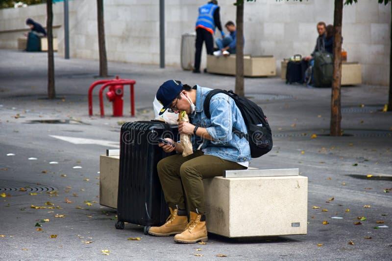 Station passagerare som väntar på drevet Man att äta briochen, bagett på bänken av original- art royaltyfria foton