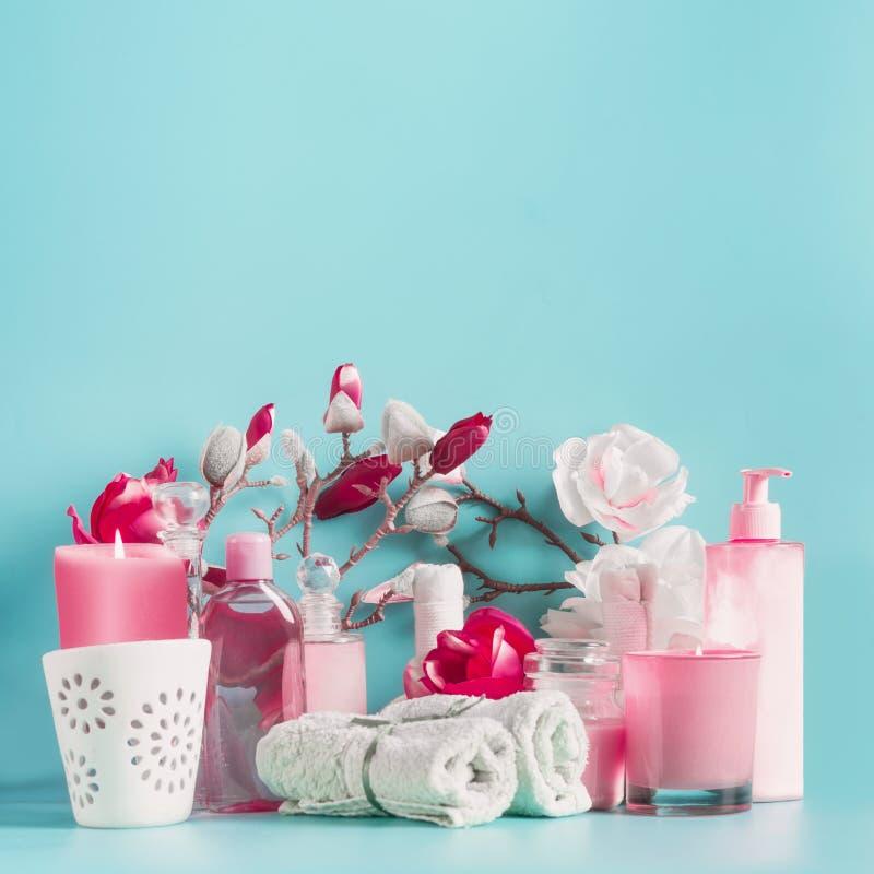 Station thermale blanche rose plaçant le fond avec des serviettes, des fleurs, des bougies et des cosmétiques de soin de corps à  photo stock