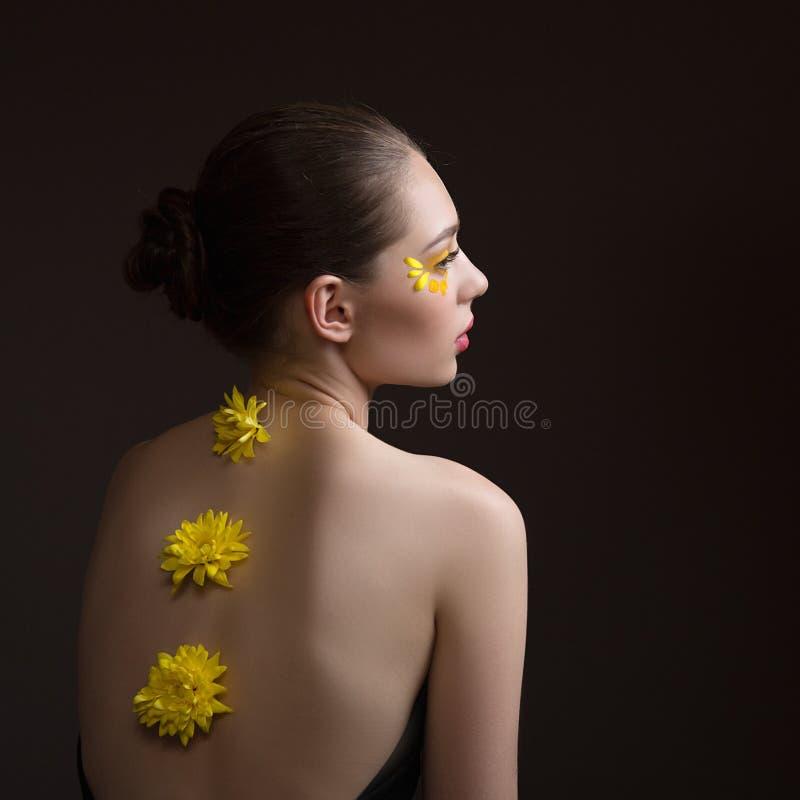 Station thermale de jeune femme Fleurs jaunes le long de son dos, visage et corps à la nuance Vue arri?re Fond fonc? photographie stock