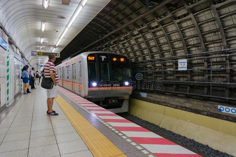 Station of Tokyo metro with approaching train and people on plat stock photo