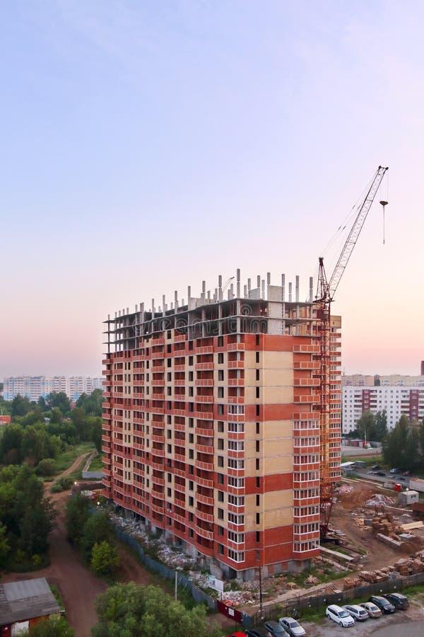 Stationair hijstoestel en de baksteen lange bouw in aanbouw royalty-vrije stock afbeelding