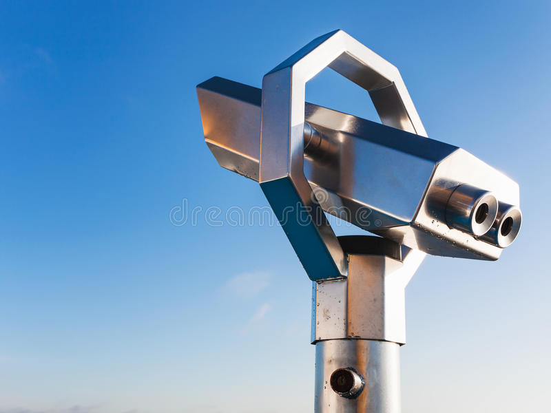 Stationary observation binoculars and blue sky. In sunny day stock image