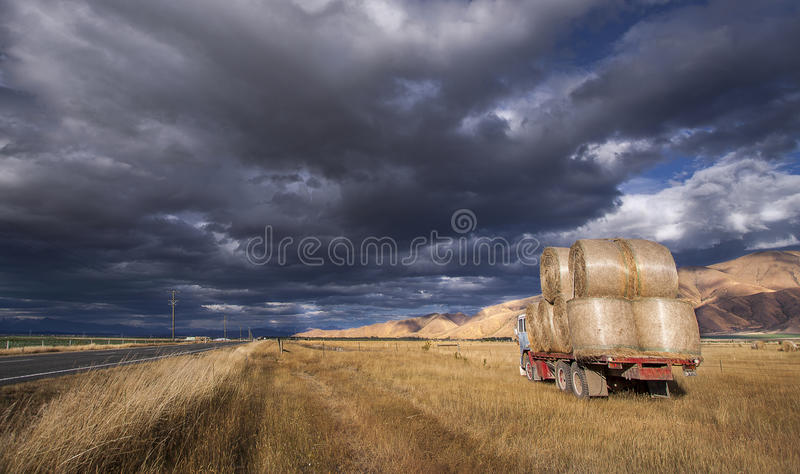 Stationary Truck Loaded With Hay Bales. Truck transporting hay bales in late afternoon light under a threatening sky in Central Otago, New Zealand royalty free stock photo