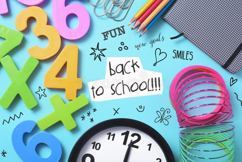 Stationery, clock and text back to school. A clock, some pencil crayon of different colors, a notepad, some paper clips, some numbers of different colors, some stock images