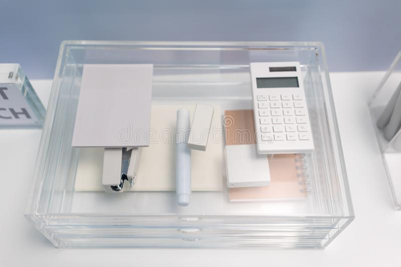 Stationery items in transparent acrylic glass organizer with drawers royalty free stock photos