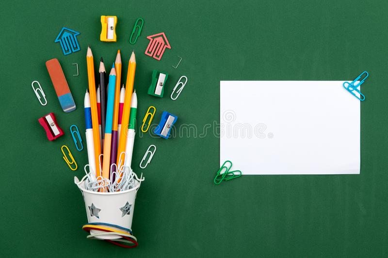 Stationery Pencils paper clip pen eraser in a white bucket. Still life on green school board background. Copy space Flat lay Top royalty free stock photography