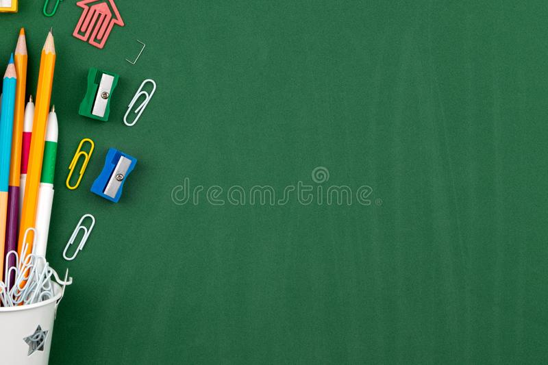 Stationery Pencils paper clip pen eraser in a white bucket. Still life on green school board background. Copy space Flat lay Top stock photography
