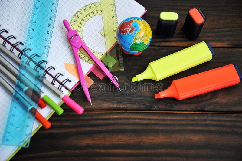 Stationery scattered on a notebook lying on a wooden table royalty free stock image