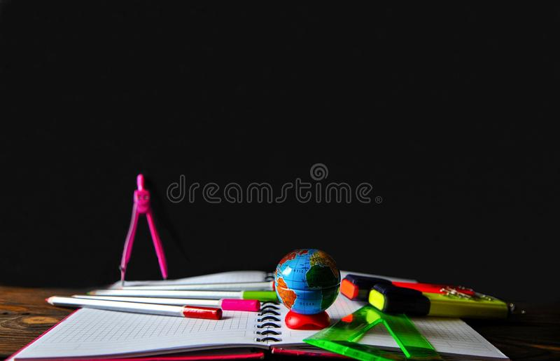 Stationery scattered on a notebook lying on a wooden table on the background of a board stock photography