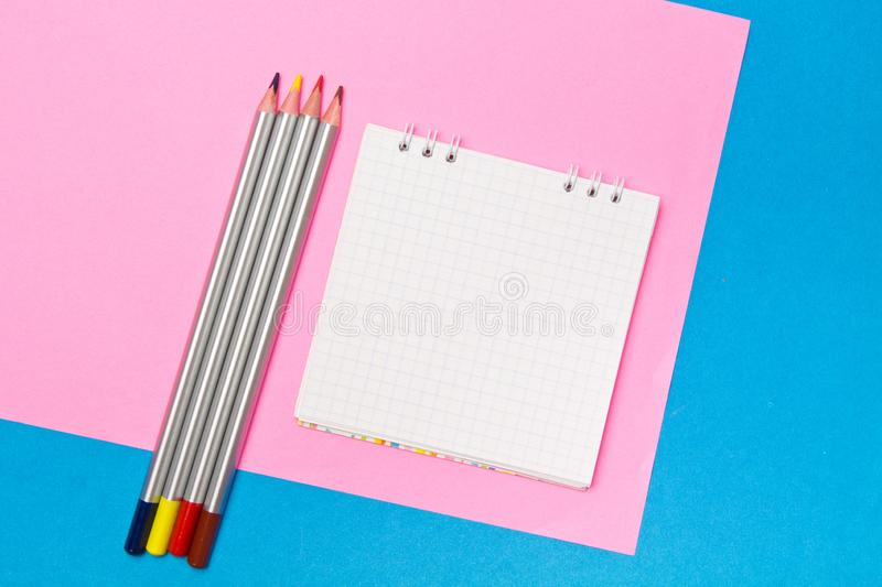 Stationery. School and office supplies on a blue and pink colored background. Selective focus.Advertising space stock photography