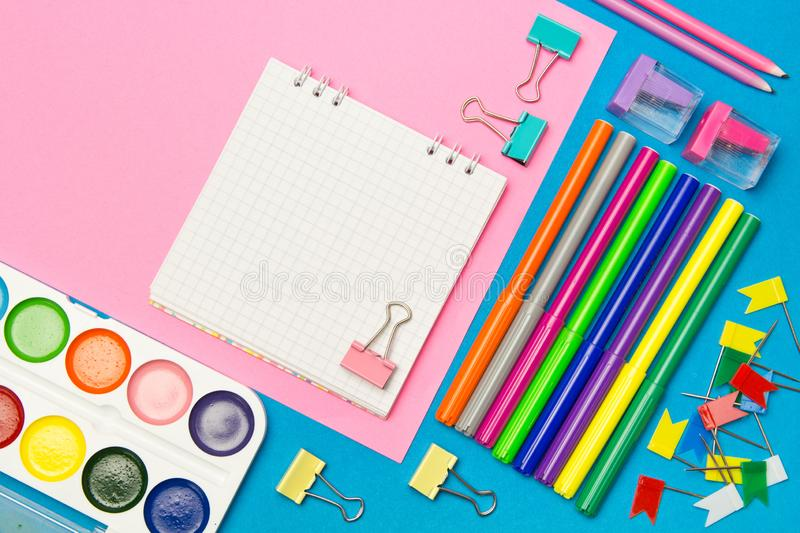 Stationery. School and office supplies on a blue and pink colored background. Selective focus.Advertising space stock photo