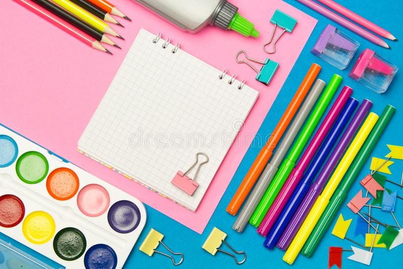 Stationery. School and office supplies on a blue and pink colored background. Selective focus.Advertising space royalty free stock image