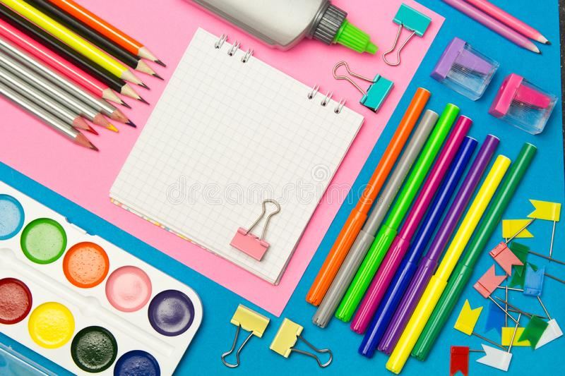 Stationery. School and office supplies on a blue and pink colored background. Selective focus.Advertising space stock images