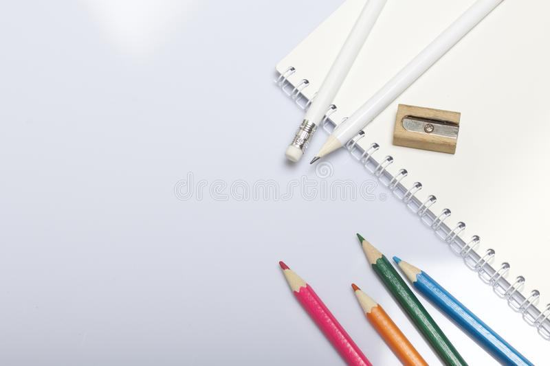Stationery for school and teaching. Notepad and pencils for writing and drawing. Sharpener for pencils. royalty free stock photos