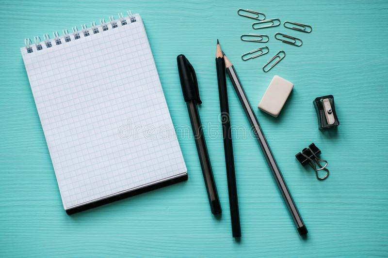 Notepad with a blank page, pen, two pencils, eraser, metal clips on turquoise background royalty free stock photos