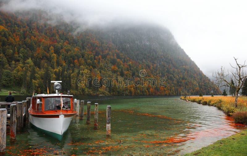 Stationnement de bateau sur le lac Konigssee avec le pilier en bois et les feuilles tombées par le bord de lac un matin brumeux b photographie stock libre de droits