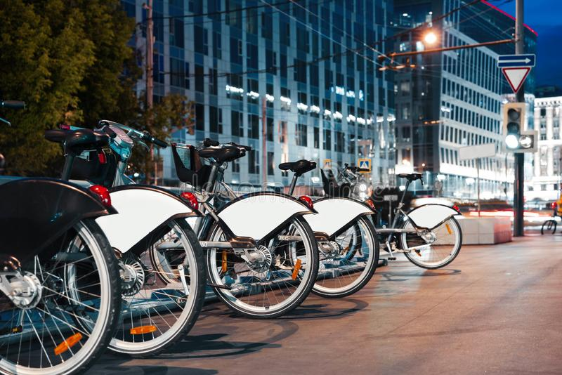 Stationnement de bicyclette à la nuit dans le centre ville Concept moderne de transport photos libres de droits