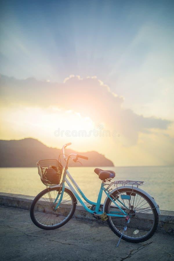 Stationnement de bicyclette de vintage sur la route vide contre le beau ligh du soleil photos libres de droits