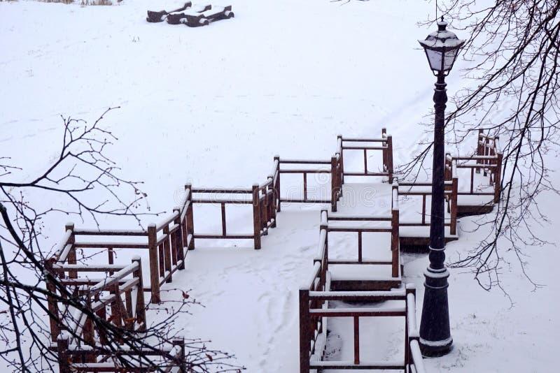 Stationnement de l'hiver escaliers couverts de neige descendant lanterne de cru du côté image libre de droits