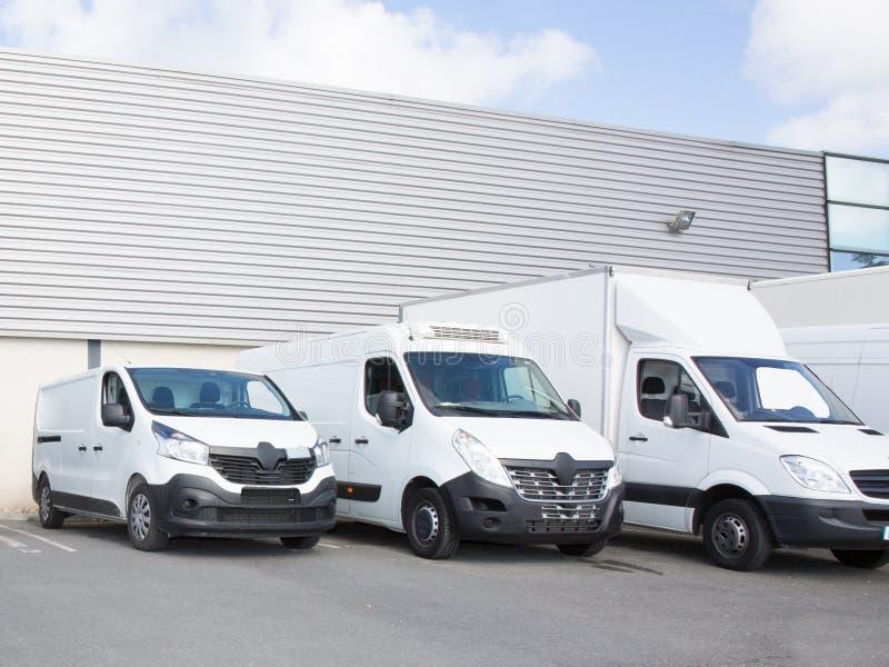 stationnement de société de la livraison avec de petits camions et fourgon images libres de droits