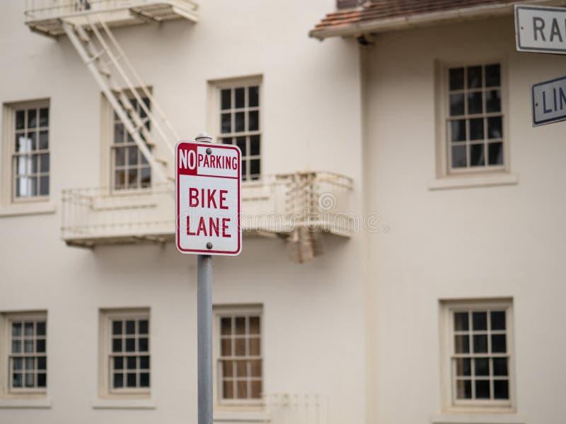 Stationnement interdit, signe de ruelle de vélo signalé devant l'entrepôt blanc images libres de droits