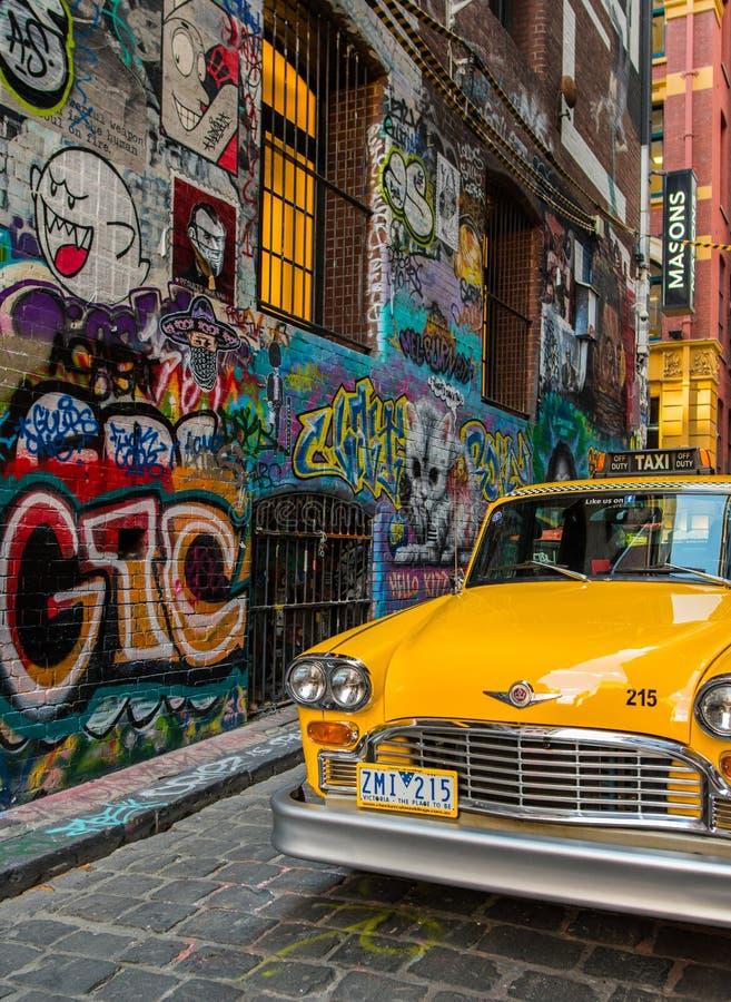 Stationnement jaune de taxi à la ruelle de bonnetier le streptocoque célèbre d'art de graffiti photo stock