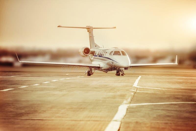 Stationnement privé d'avion à réaction à l'aéroport Avion privé au coucher du soleil orange images stock
