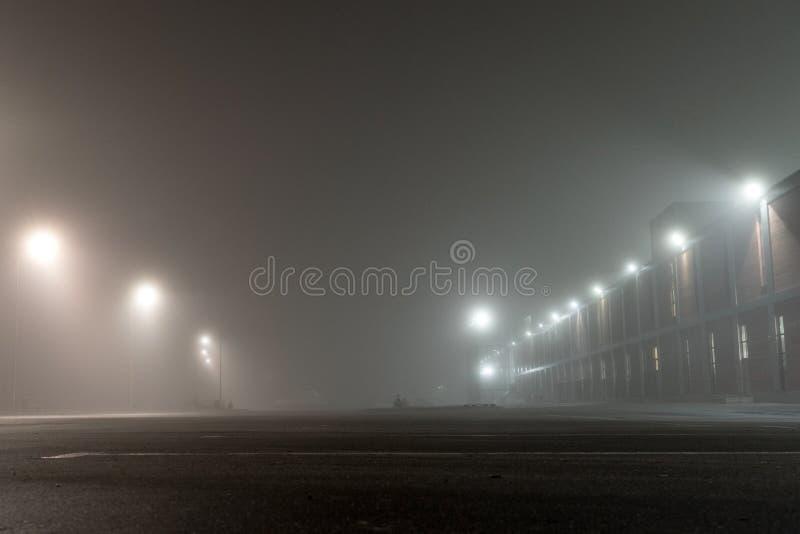 Stationnement urbain vide et réverbères de voiture la nuit brumeux Vieux immeuble de brique et lanternes industriels sur la rue i photographie stock libre de droits