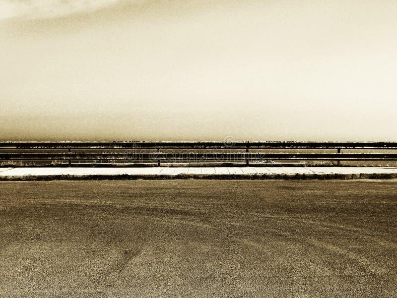 Stationnement vide avec la rambarde, tonalité grenue de sépia photo libre de droits