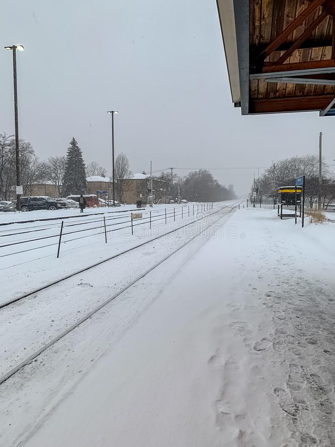 Stationplatform in de voorsteden van Chicago tijdens sneeuwstorm, met forens het lopen langs sporen stock foto
