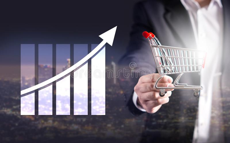 Statistics, analytics and financial report. Success and growth concept. Growing graph. Business man holding miniature shopping cart. Double exposure stock image