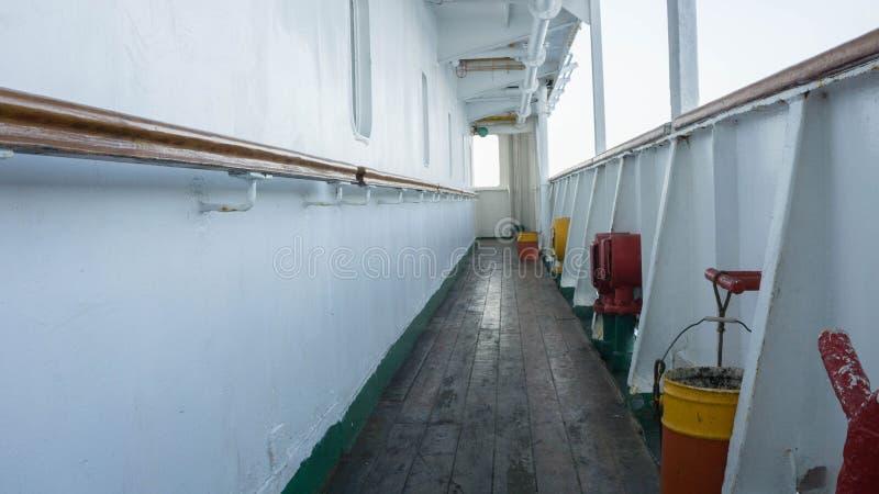 Statku pokład z wietrzejącym starym drewnianym łódkowatym poręczem na bocznej biel ścianie i podłoga zdjęcie royalty free