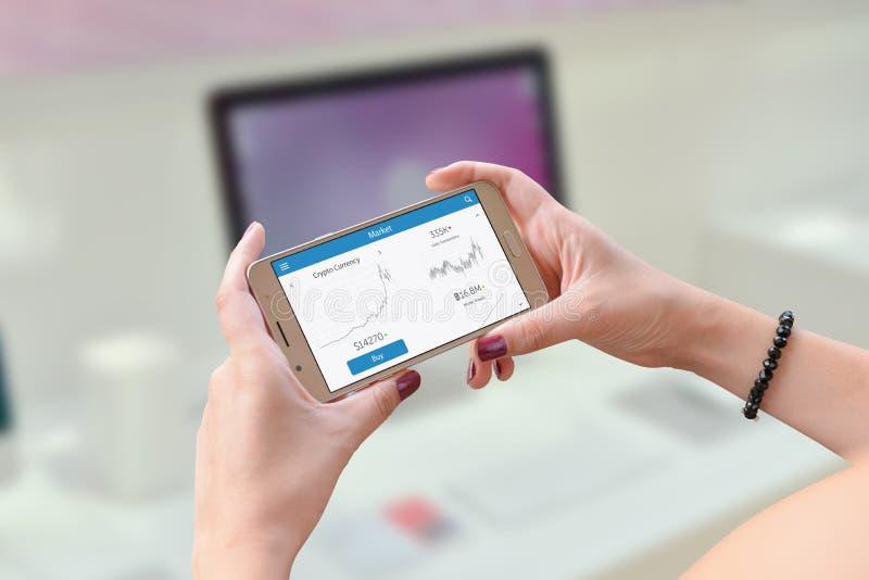 Stats cripto di valuta dello Smart Phone e dell'orologio della tenuta della donna fotografia stock libera da diritti