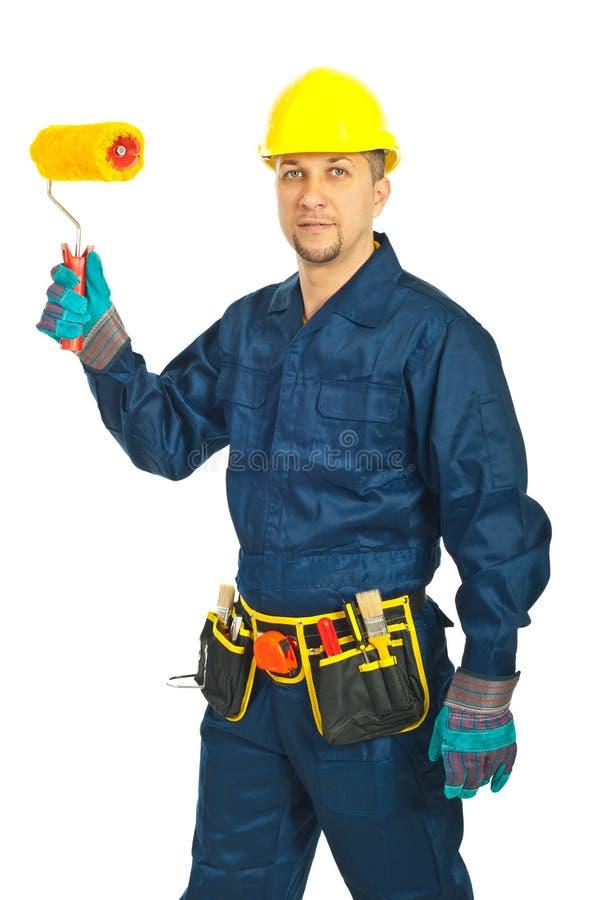 Stattlicher Arbeiter mit Lackrolle stockfotos