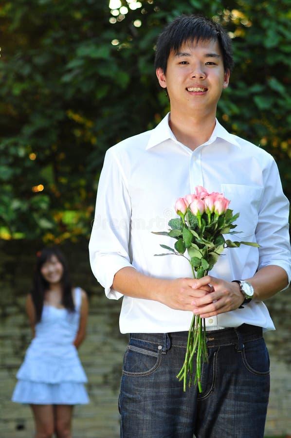 Stattlicher asiatischer Mann, der ein Bouguet der Blumen anhält stockfoto