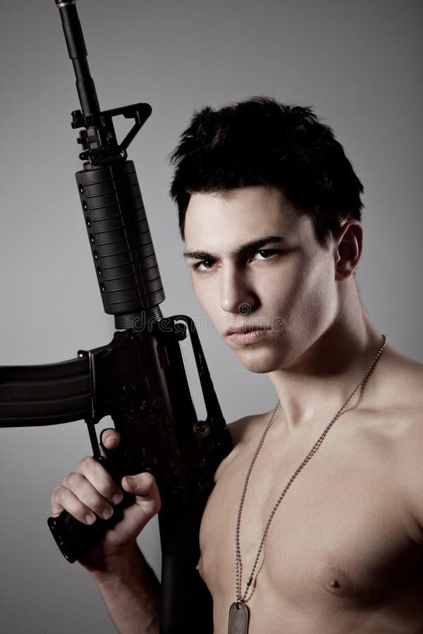 Stattlicher bare-chested Soldat hält ein Gewehr an lizenzfreies stockbild