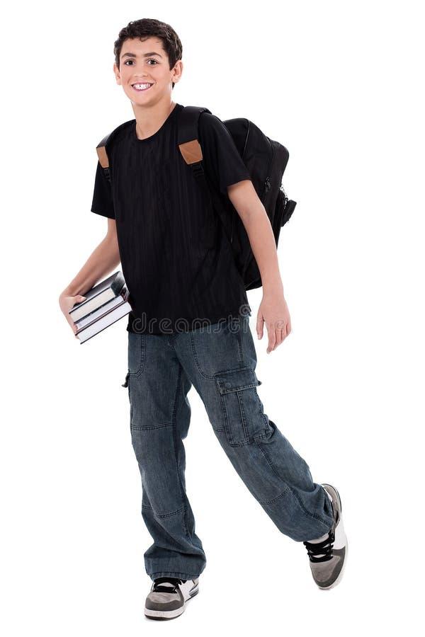 Stattlicher Jugendlichjungenkursteilnehmer mit Büchern in der Hand stockfoto