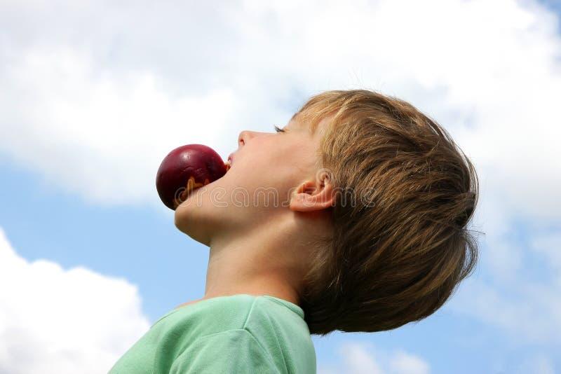 Stattlicher Junge, der Spaß mit einem Pfirsich bildet stockbilder