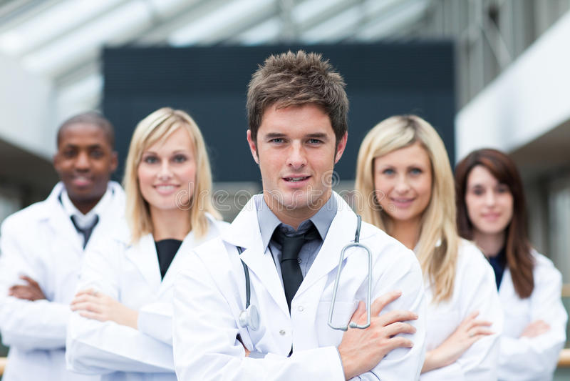Stattlicher junger Doktor, der sein Team führt lizenzfreies stockbild