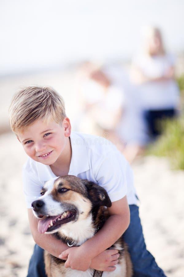 Stattlicher junger Junge, der mit seinem Hund spielt lizenzfreie stockfotografie