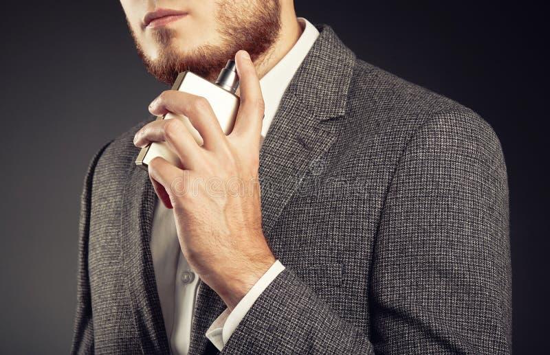 Stattlicher junger Mann, der Duftstoff verwendet lizenzfreies stockfoto