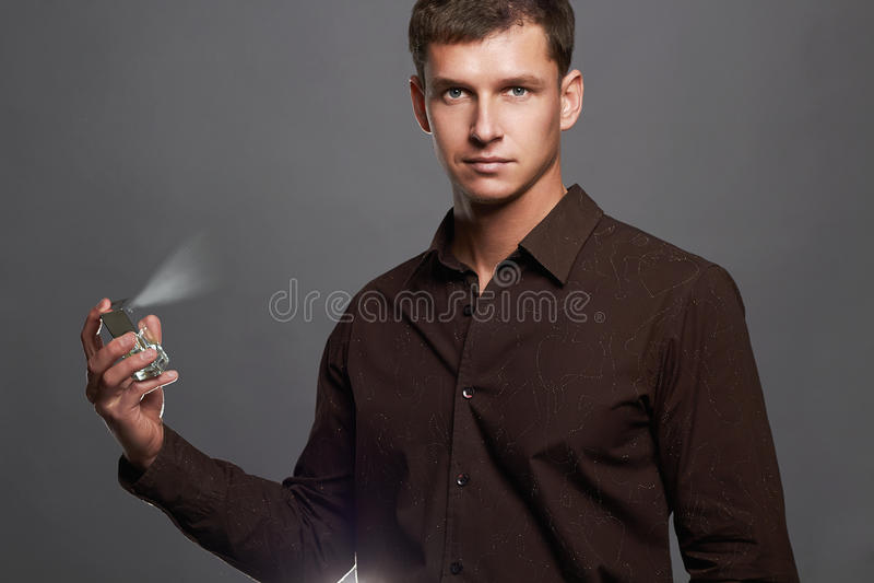 Stattlicher junger Mann, der Duftstoff verwendet Parfümflasche und Sprühduft stockfotografie